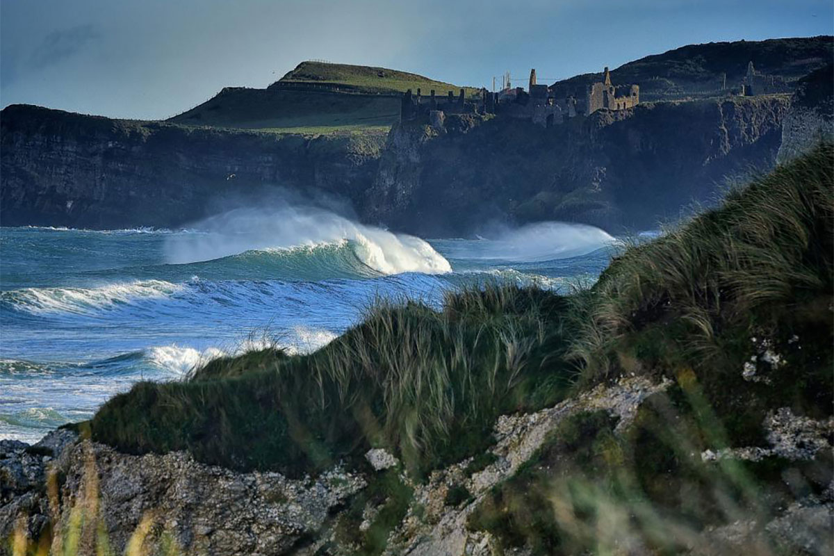 Big waves in front of Dunluce Castle near the Giant's Causeway in Antrim